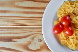 Macaroni in a plate on a wooden back