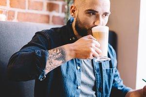 Man drinking coffee, working
