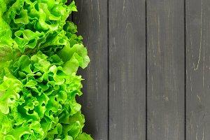 Fresh lettuce leaves border on wood
