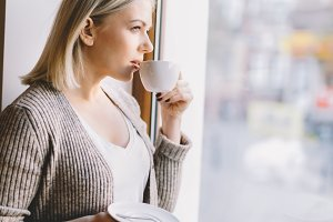 Young woman drinking coffee, looking