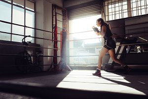 Female boxer training inside