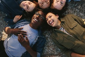 Diverse friends lying on ground