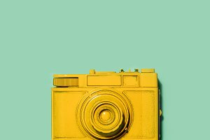 Yellow camera laying on a green back