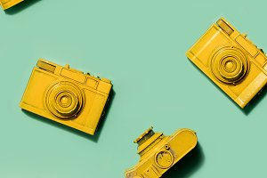 Yellow cameras on green background