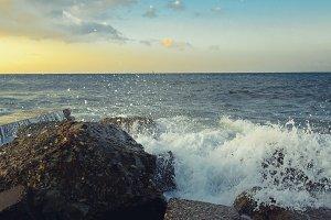 Waves break on coastal stones