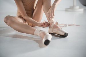 Beautiful little ballerina puting on foot pointe shoes