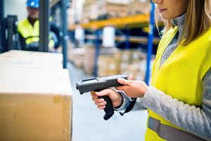 Warehouse woman worker with barcode scanner.