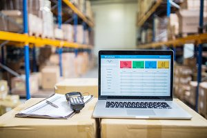 Laptop and barcode scanner on boxes in a warehouse.