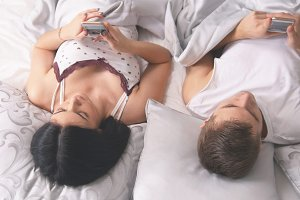 Young attractive couple lying on the bed with smartphones and having rest together, everyone looks in his phone