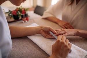 Manicurist shaping nails of client