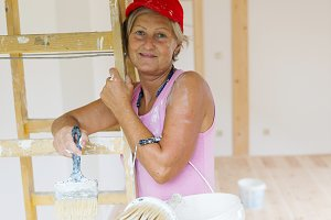 Senior woman painting the house.