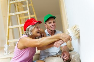 Senior couple painting the house.