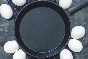 Black cast-iron frying, chicken eggs