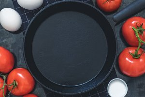 Black cast-iron frying, red tomatoes