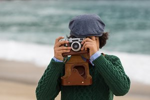 Boy with vintage camera at the beach