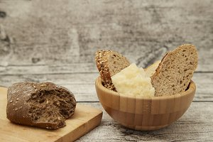 Fresh bread on board wooden bg