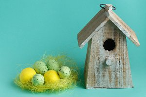 color Easter eggs in nest on turquoise background with wooden vintage birdhouse
