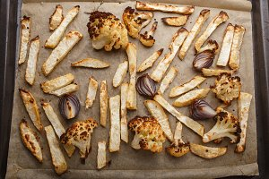 baked vegetables on a baking sheet - celery, cauliflower and red onion