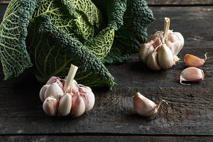 Savoy cabbage and fresh garlic on a dark wooden table