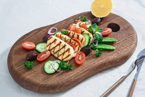 grilled hallumi cheese on wooden cutting board