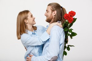 Portrait of an attractive young man hiding flowers from his girlfriend before giving her a surprise over white isolated background.