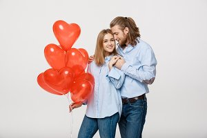 Portrait of young fashionable caucasian couple with balloons heart hugging at each other over isolated white background.