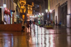 People walking  in rainy evening
