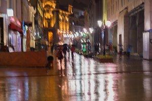 People walking  in rainy evening