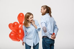 Portrait of Young handsome guy gives a ring to a girl on a white background with red heart air balloons.