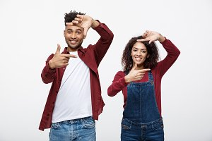 Happy young African American couple looking through a finger frame and smiling while standing isolated on white.