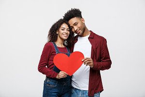 Young happy African American couple in love holding red paper heart.