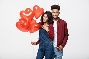 Close up attractive African American couple huging and holding red heart balloon.