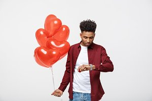 Handsome African American holding heart balloon and checking time on his watch.