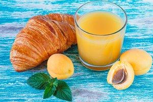 Orange apricots, croissant, juice