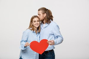 Portrait of young happy couple in love holding red paper heart.