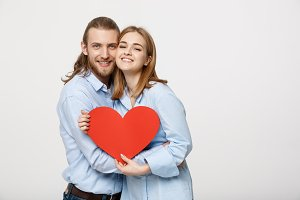 Portrait of happy cute couple in love enjoys Valentine's Day. A man with a beard and a woman with blond short hair holding red heart paper.