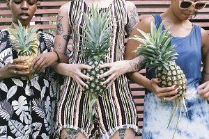 women holding pineapple