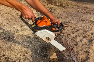 A man saws a log with a chainsaw.