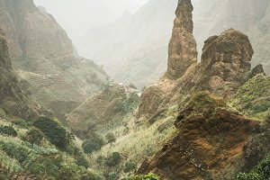 Mountain peaks of Xo-Xo valley of Santa Antao island, Cape Verde. Many cultivated plants growing in the valley between high rocks. Arid and erosion mountain peaks sun light. Sahara dust in the air