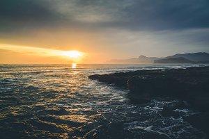 Wavy sea at sunset rocky coast