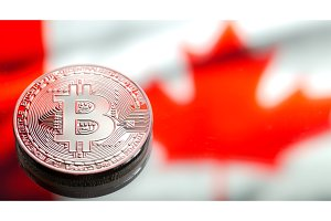 coins Bitcoin, against the background of Canada flag, concept of virtual money, close-up. Conceptual image.