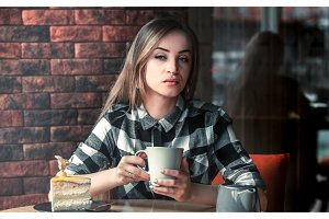 Beautiful girl drinks tea in a cafe