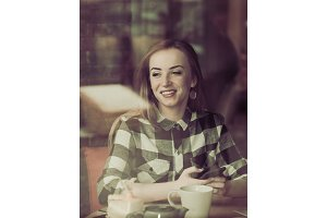Beautiful girl with a phone in a cafe at the table,
