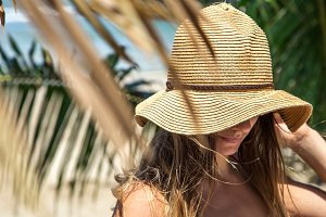 beautiful girl in a summer hat on a background of palm leaves on the beach, holiday concept