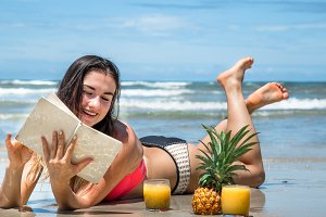 beautiful girl lying on the beach reading a book with fresh summer drinks and tropical fruits, holiday