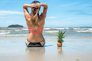 beautiful girl sitting on the beach on exotic landscapes and pineapple