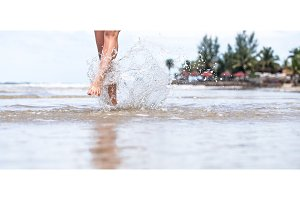 beautiful female legs on the beach with water splashing