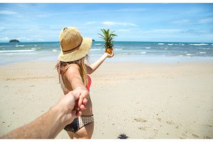 beautiful girl in swimsuit and pineapple walks on the beach holding the hand of the guy