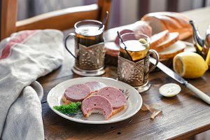 Sandwiches with sliced sausage on a plate with tea