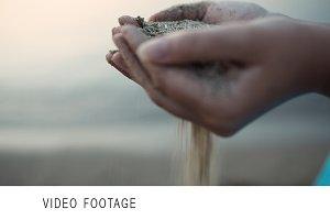 Sea sand running through a womans